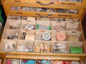 Das Foto zeigt eine Schublade mit vielen kleinen Fächern in den sich unterschiedliche Ersatzteile befinden wie Nähfaden und andere